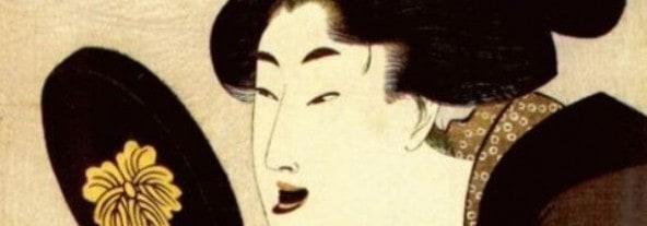 A geisha checking her black-painted teeth in a mirror