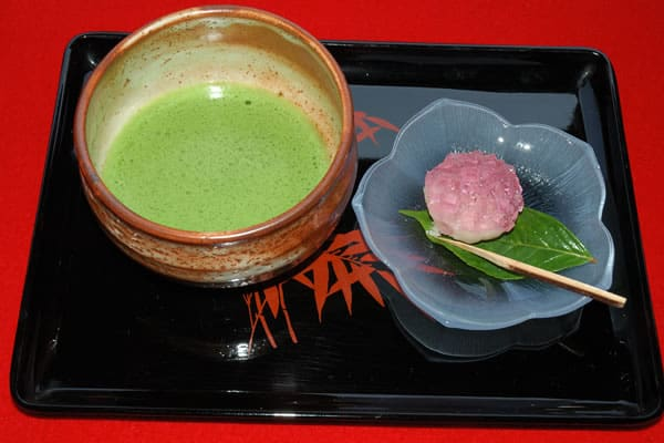 A bowl of Japanese green tea and a rice and bean paste cake with a little stick to eat it with
